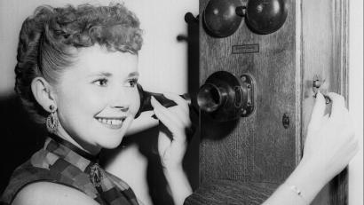 Dolores Cady cranks the handle of an old fashioned telephone.