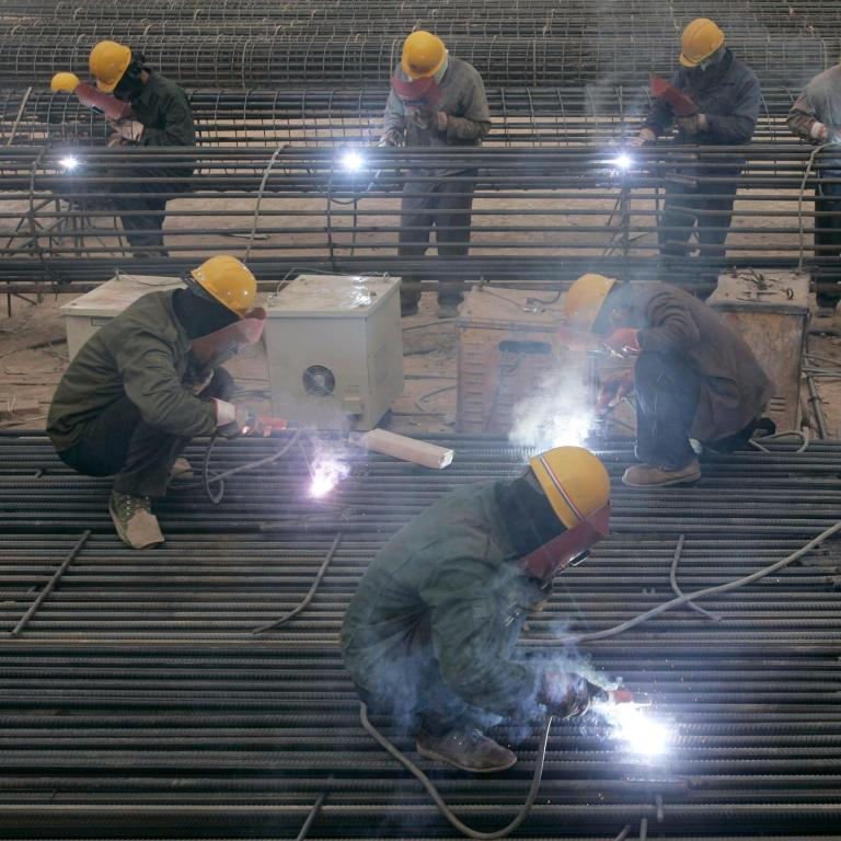 Labourers weld steel bars at a construction site in Taiyuan, Shanxi province, China.