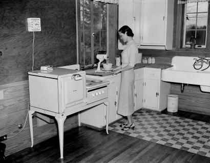A housewife is shown as she prepares a meal in her all-electric kitchen in Morris, Tenn.