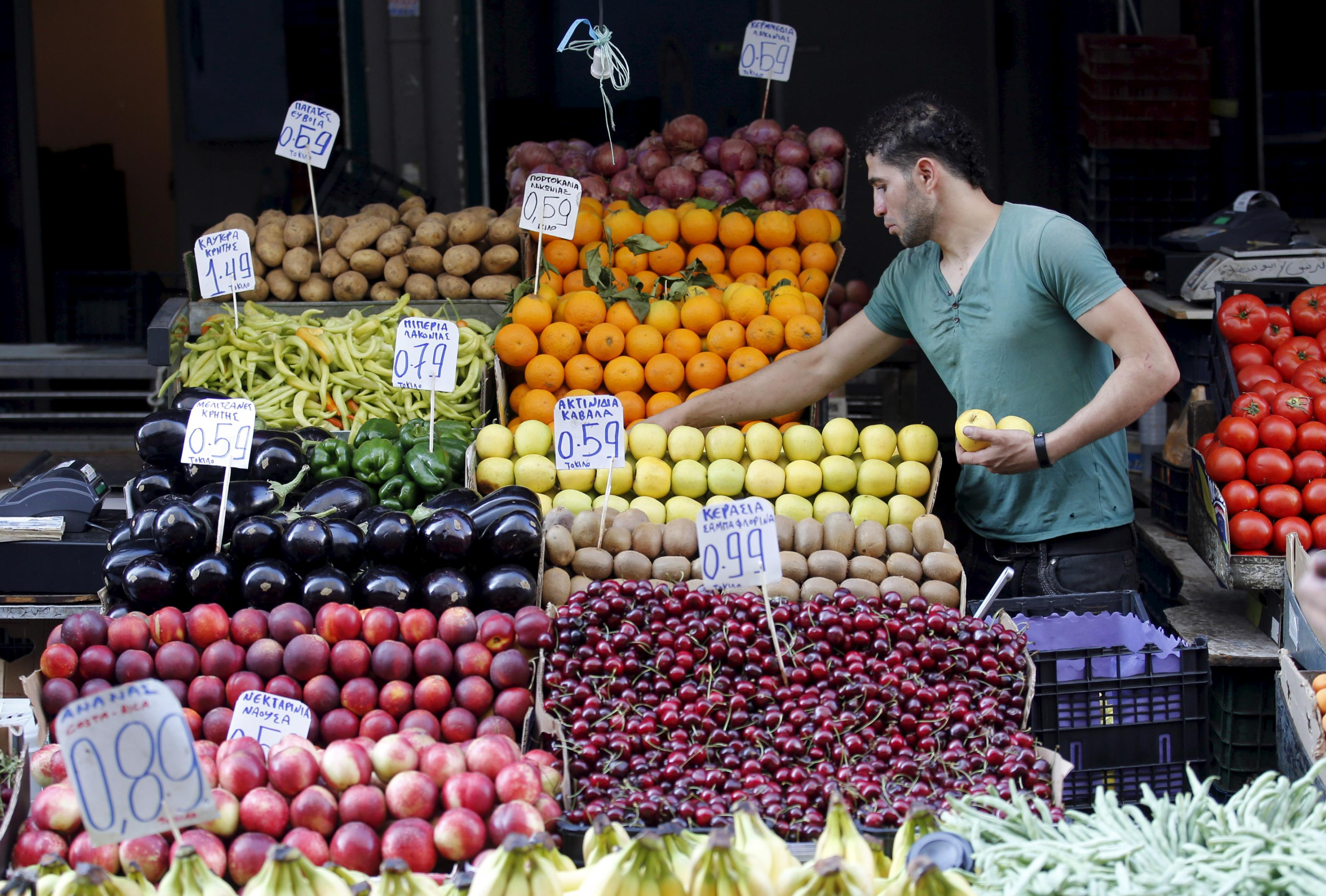 A vendor displays fruits in his shop in a local market in central Athens, Greece.