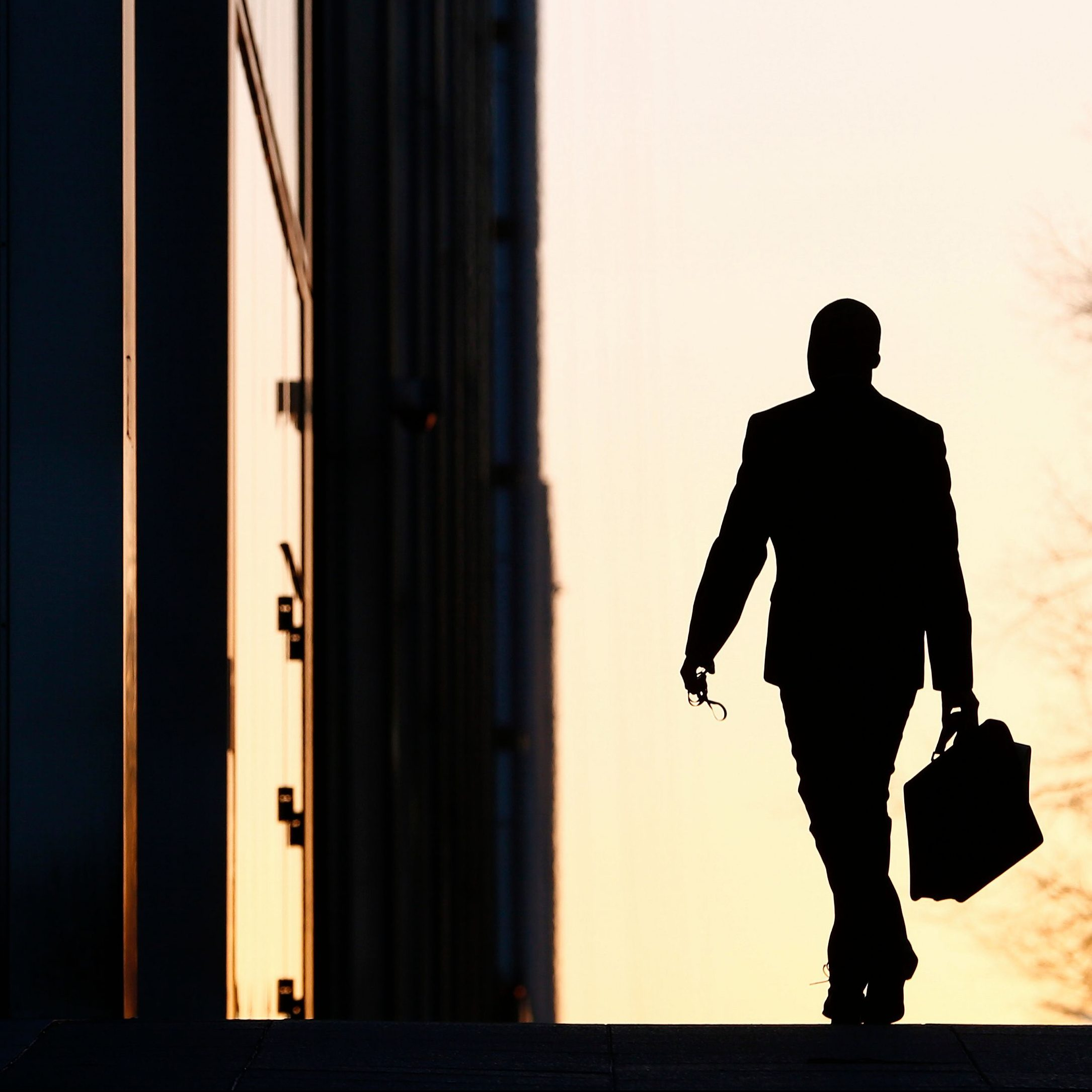 A worker arrives at his office in the Canary Wharf business district in London February 26, 2014.