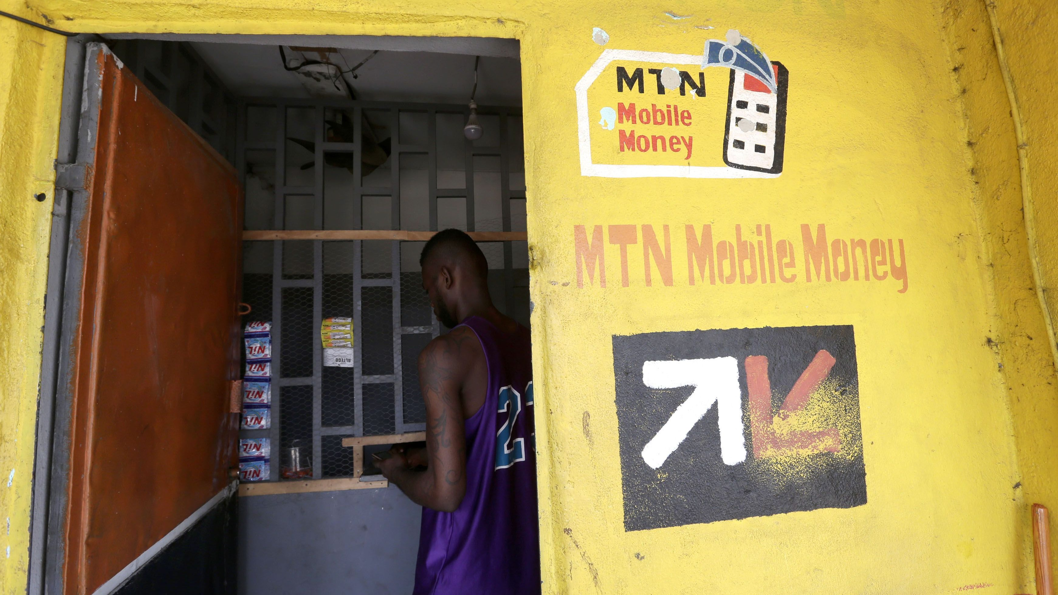 A man withdraws money at an MTN Money cashier booth, in Abidjan, Ivory Coast, 10 May 2017. This mobile phone-based payment system allows customers to use their phones to pay their bills or to transfer funds to any other phone subscriber.