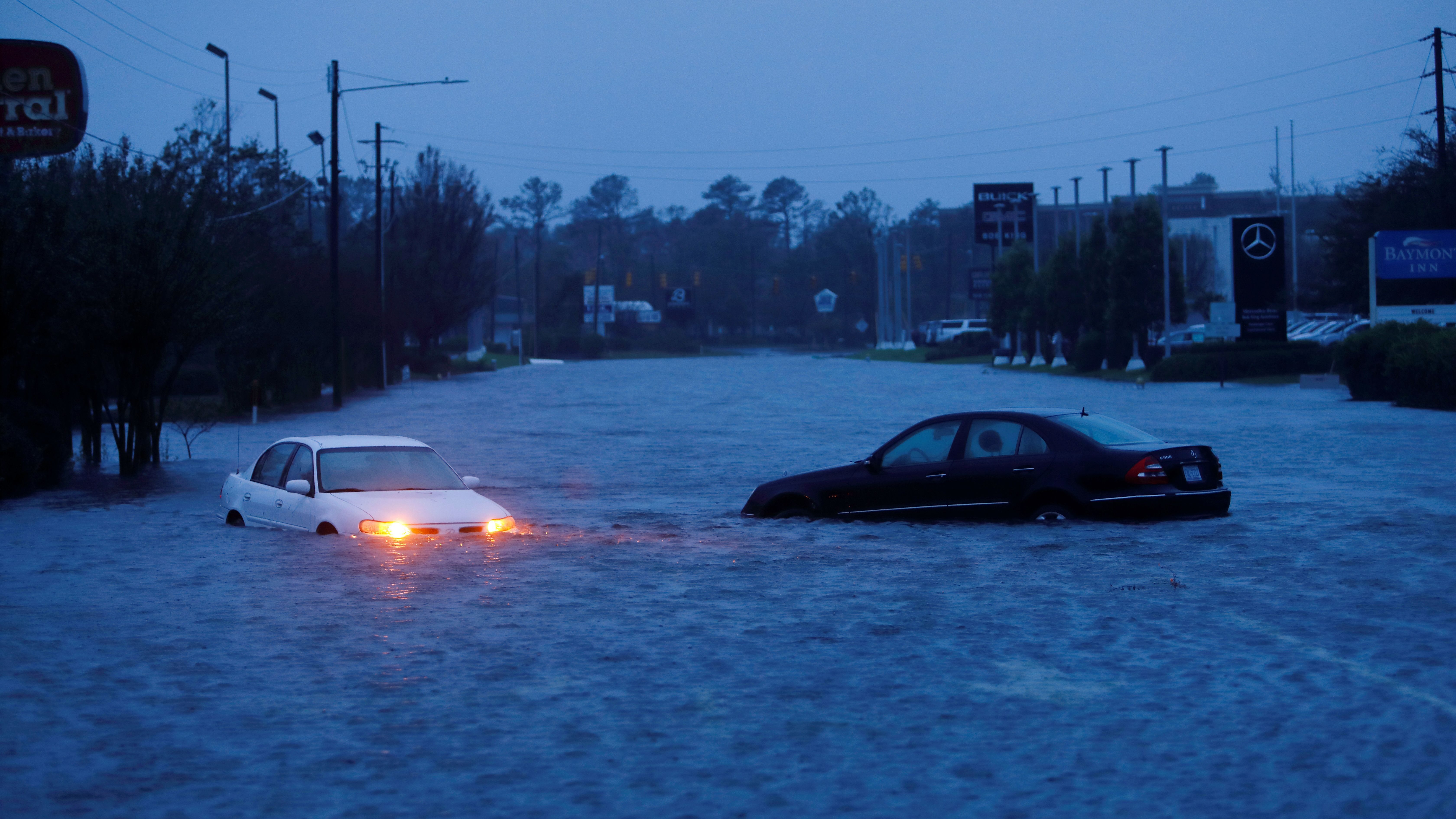An abandoned car's hazard lights continue to flash as it sits submerged in a rising flood waters during pre-dawn hours after Hurricane Florence struck in Wilmington, North Carolina, U.S., September 15, 2018.