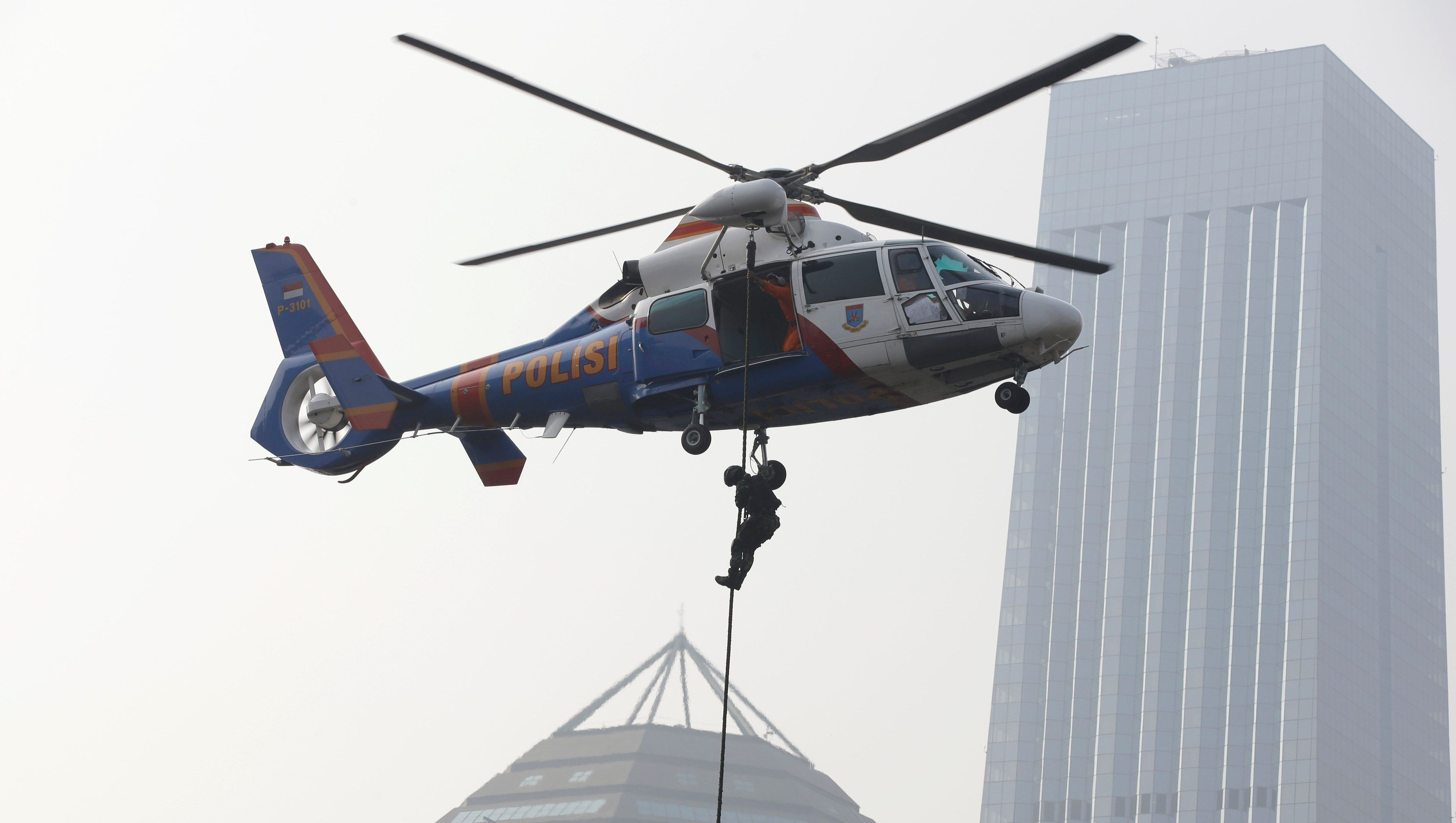 Indonesian police rappel down from a helicopter during an anti-riot exercise as part of security preparations for the 2018 Asian Games in Jakarta, Indonesia, Tuesday, July 31, 2018. (AP Photo/Achmad Ibrahim)