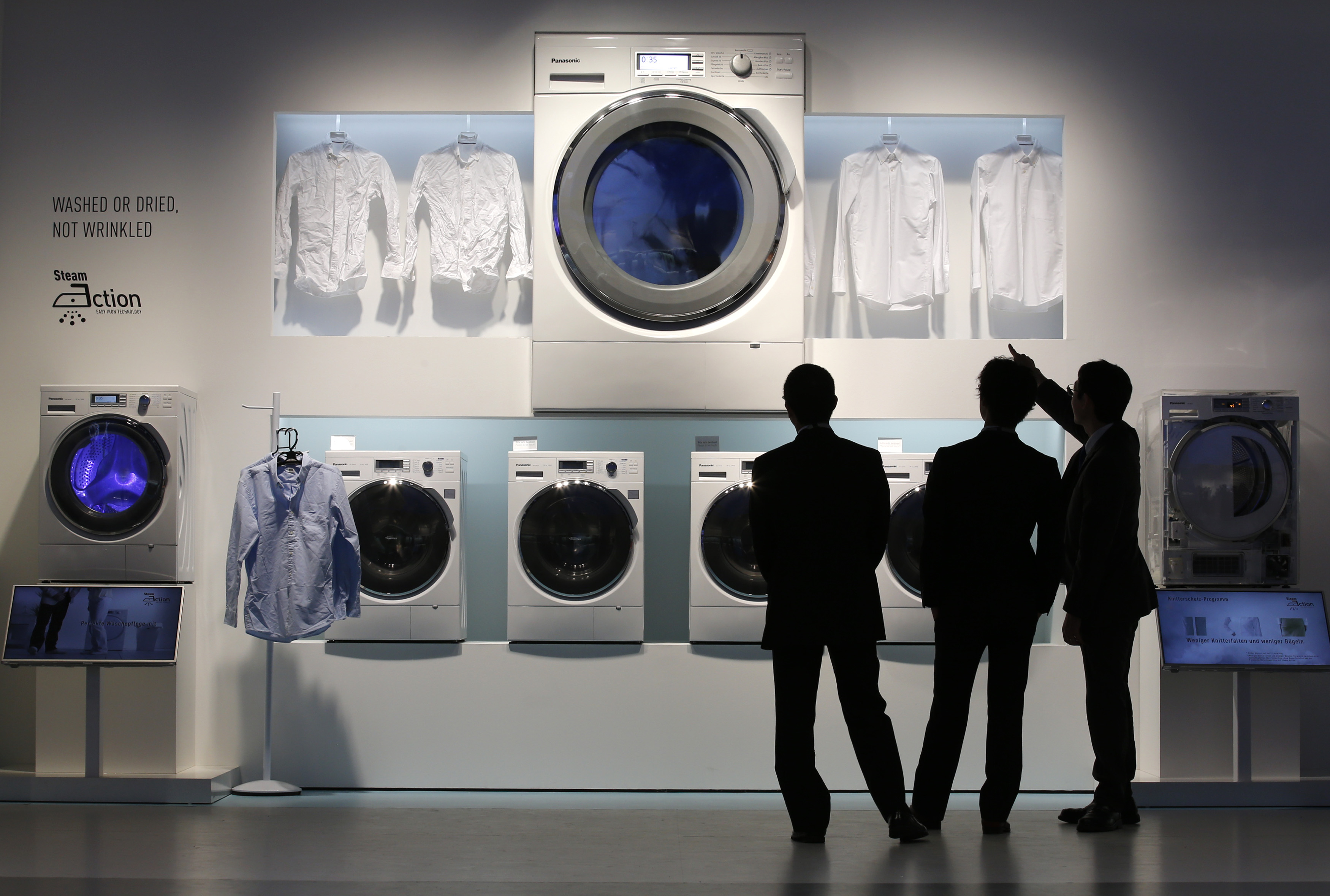 People look at a washing machine during a media preview at the Panasonic booth at the IFA consumer electronics fair in Berlin, September 4, 2013. The IFA consumer electronics and home appliances fair will open its doors to the public from September 6 till 11 in the German capital. REUTERS/Fabrizio Bensch (GERMANY - Tags: SCIENCE TECHNOLOGY TPX IMAGES OF THE DAY) - BM2E9941BCY01