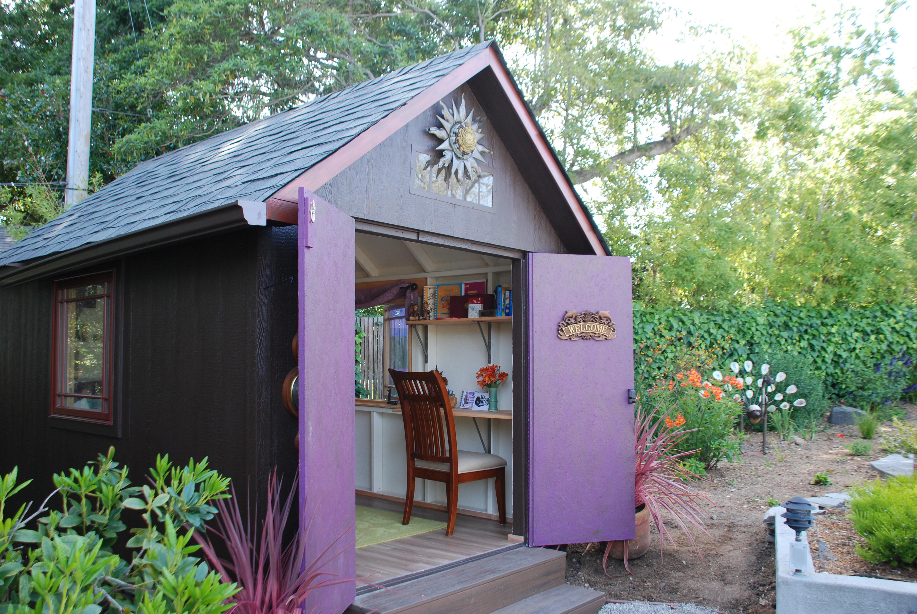 A backyard she shed with a home office inside.