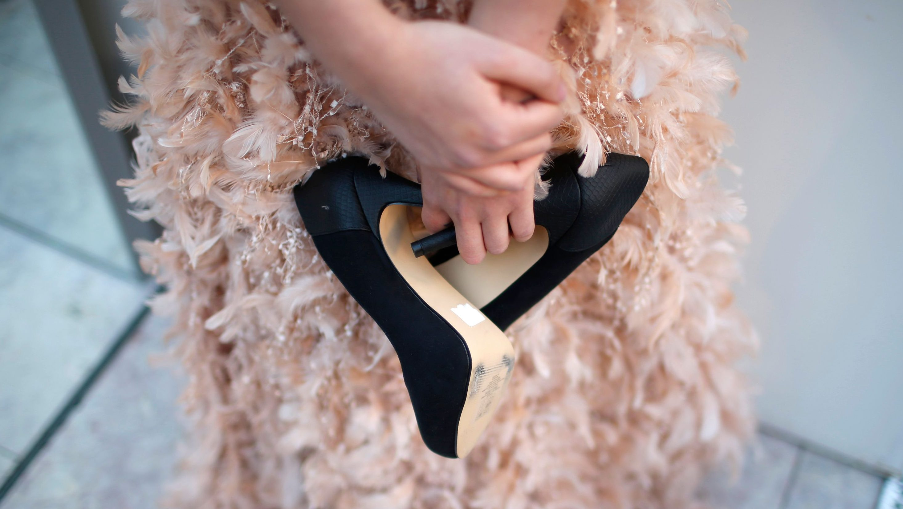A model holds her high heel shoes.