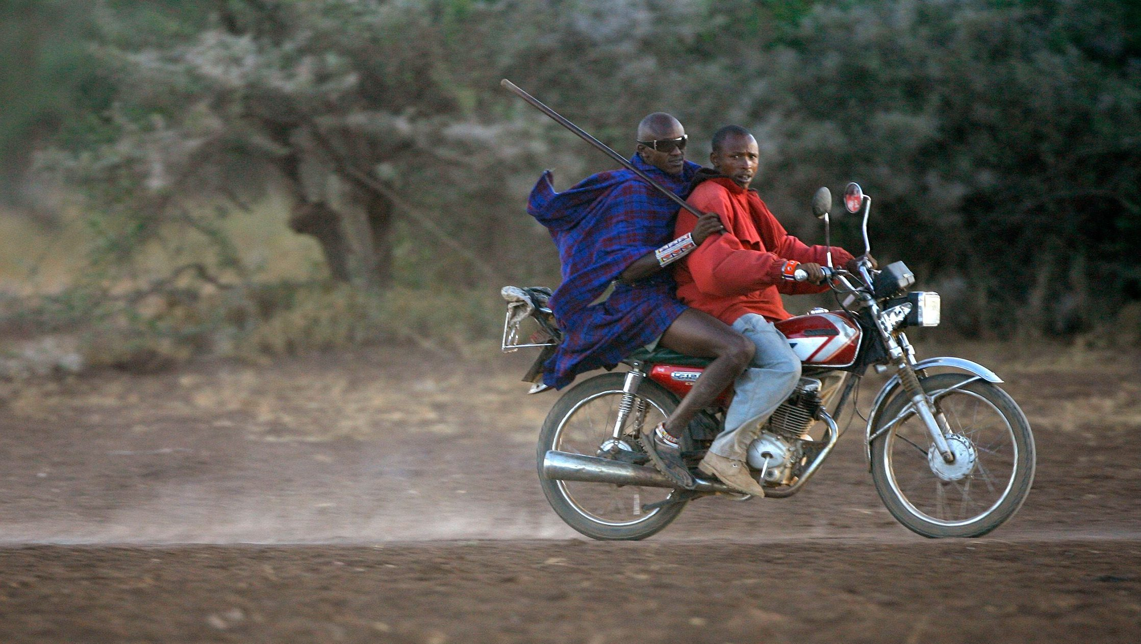 Masai men ride on a motorcycle in the Amboseli national park, Kenya, March 21 2007.