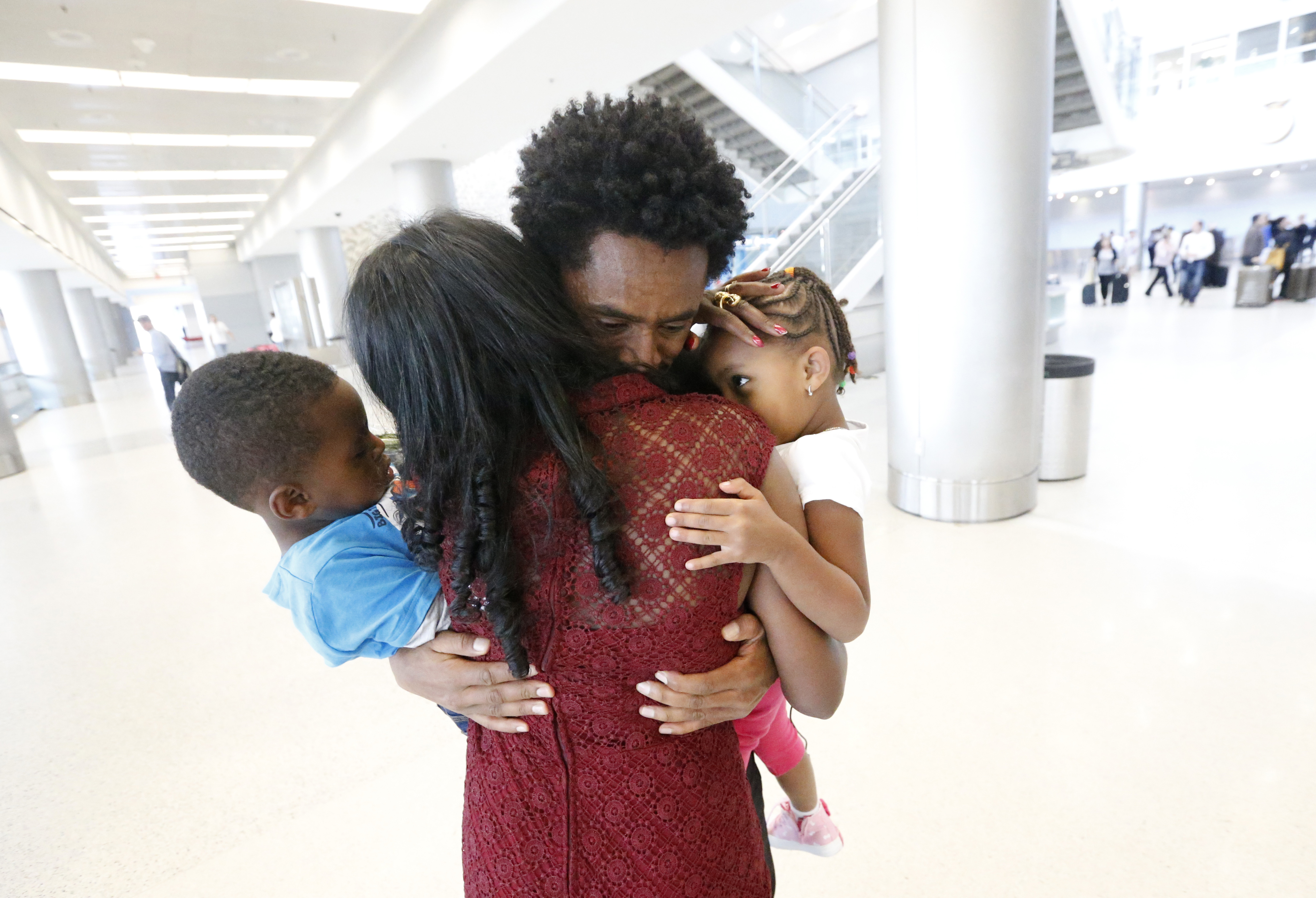 Olympic silver medalist Feyisa Lilesa, rear, of Ethiopia, hugs his wife Iftu Mulia, his daughter Soko, right, 5, and son Sora, left, 3, while picking up his family at Miami International Airport, Tuesday, Feb. 14, 2017, in Miami. Lilesa arrived in the U.S. on a special skills visa, which allows him to train and compete until January. His wife, son, daughter and brother joined him in Miami Tuesday.