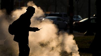 FILE - In this Nov. 30, 2012 file photo, a pedestrian looks at his phone near steam vented from a grate near the Philadelphia Museum of Art on a cold morning in Philadelphia. Every time a person shops online or at a store, loyalty cards linked to phone numbers or email addresses can be linked to other databases that may have location data, home addresses and more. Voting records, job history, credit scores (remember the Equifax hack?) are constantly mixed, matched and traded by companies in ways regulators haven't caught up with. (AP Photo/Matt Rourke, File)