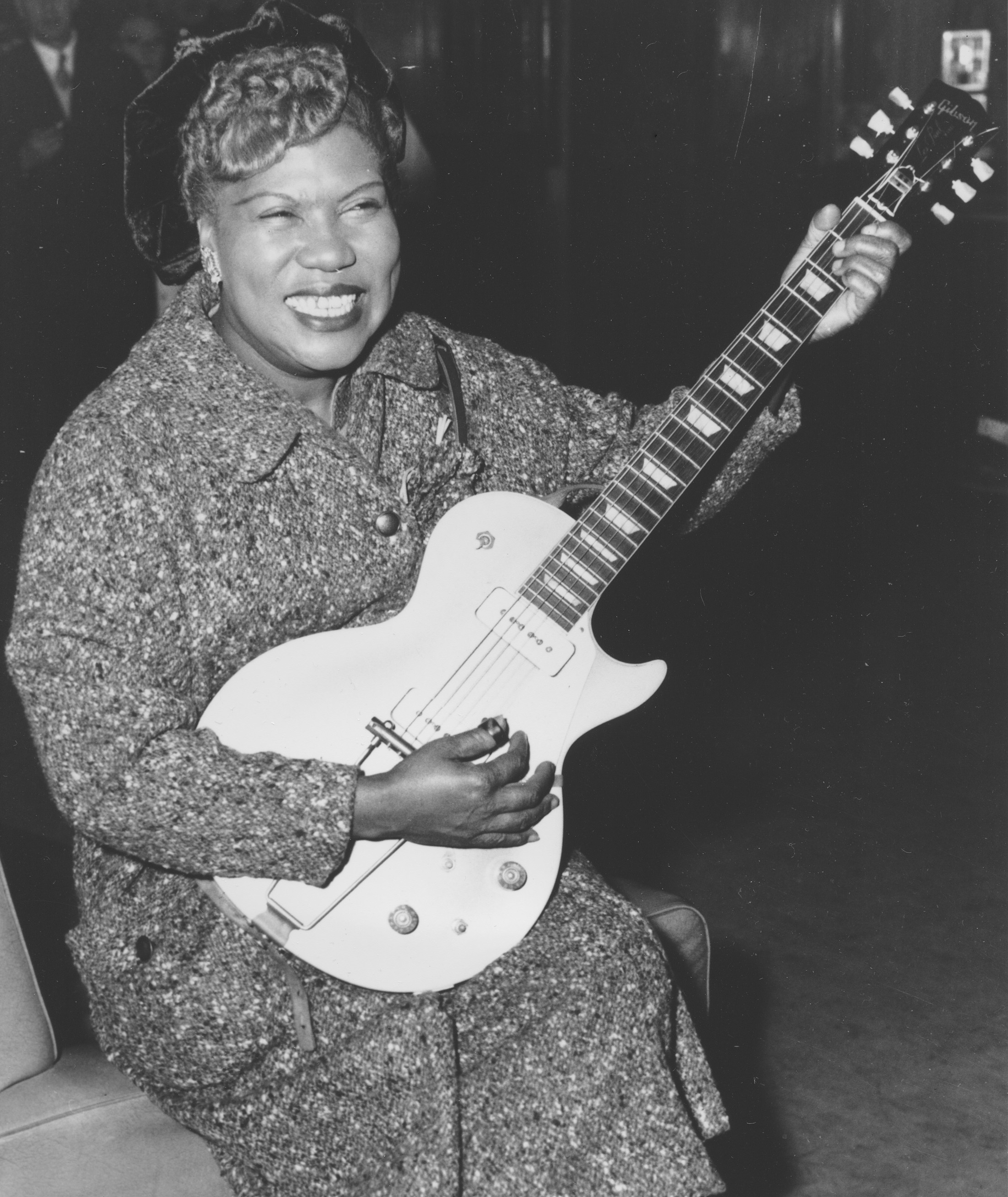 Sister Rosetta Tharpe, guitar-playing American gospel singer, gives an inpromptu performance in a lounge at London Airport, following her arrival from New York on November 21, 1957. (AP Photo)