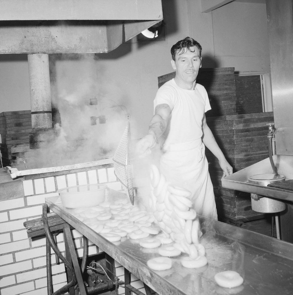 Steaming bagels are scooped out of the water in which they were boiled for two minutes and dumped onto a stainless steel drain board by Walter Scheuttig at the bagel bakery in Laurelton, Queens, New York City ,Nov. 15,1963. They will be transferred to cedar boards for baking. (AP Photo/Dan Grossi)