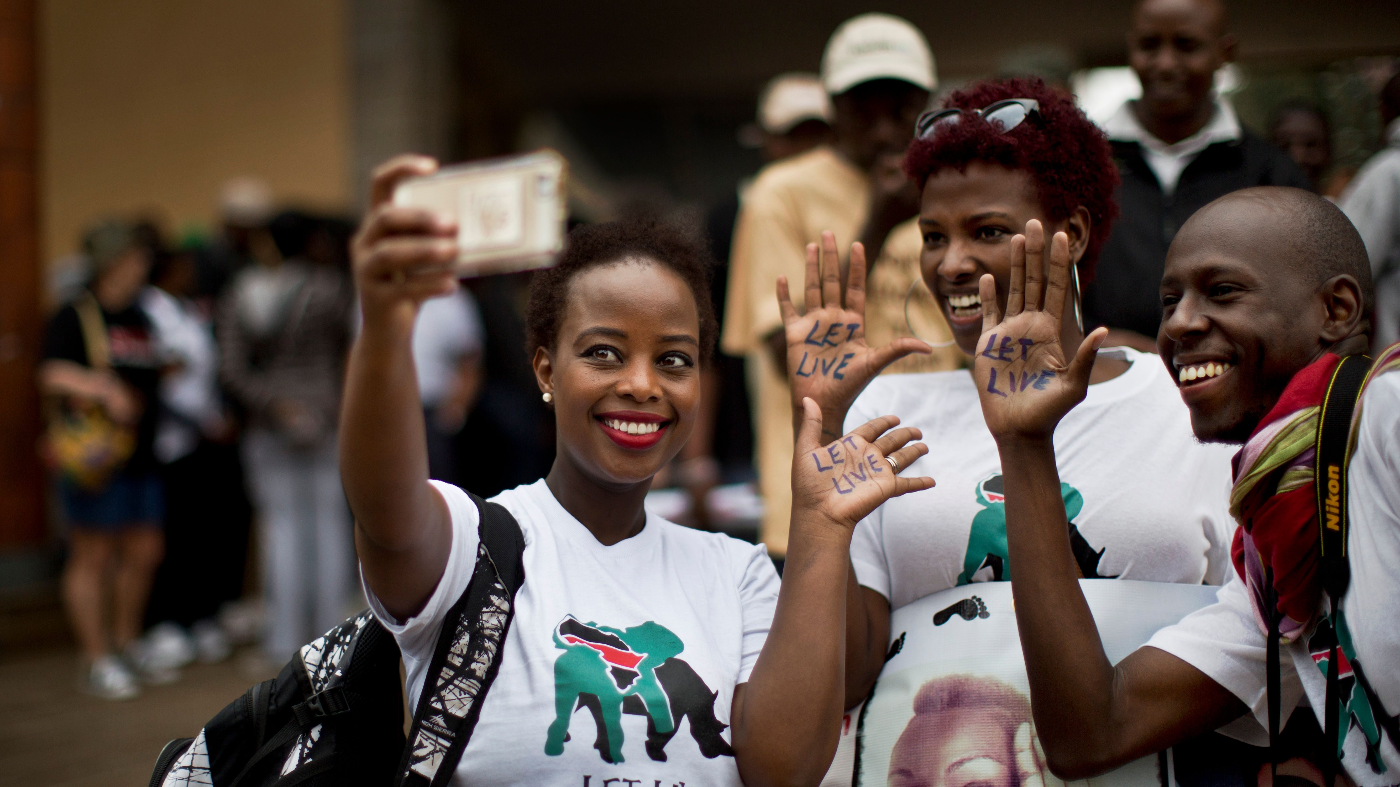 """Demonstrators take a """"selfie"""" with their smartphone and display the message """"Let Live"""" on the palms of their hands as they take part in the """"Global March for Elephants and Rhinos"""" to raise awareness for their plight, in Nairobi, Kenya Saturday, Oct. 4, 2014. Organisers of the global march, which they hope will take place in over 100 cities across the world, say it is a collaboration between many wildlife conservation organisations aiming to save elephants and rhinos from extinction by poachers and call for a ban on the trade of ivory and rhino horn."""