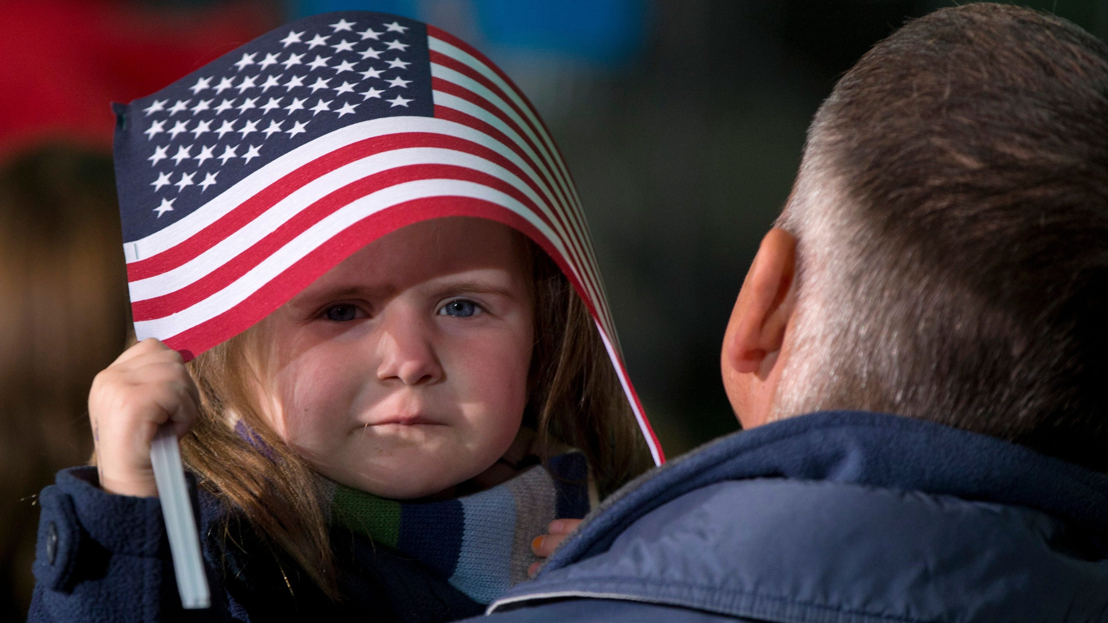 A little girl takes shelter under and American Flag before President Barack Obama arrives to speak at a campaign event at the Franklin County Fairgrounds, Friday, Nov. 2, 2012, in Hilliard, Ohio, before heading to another campaign stop in in Springfield, Ohio.
