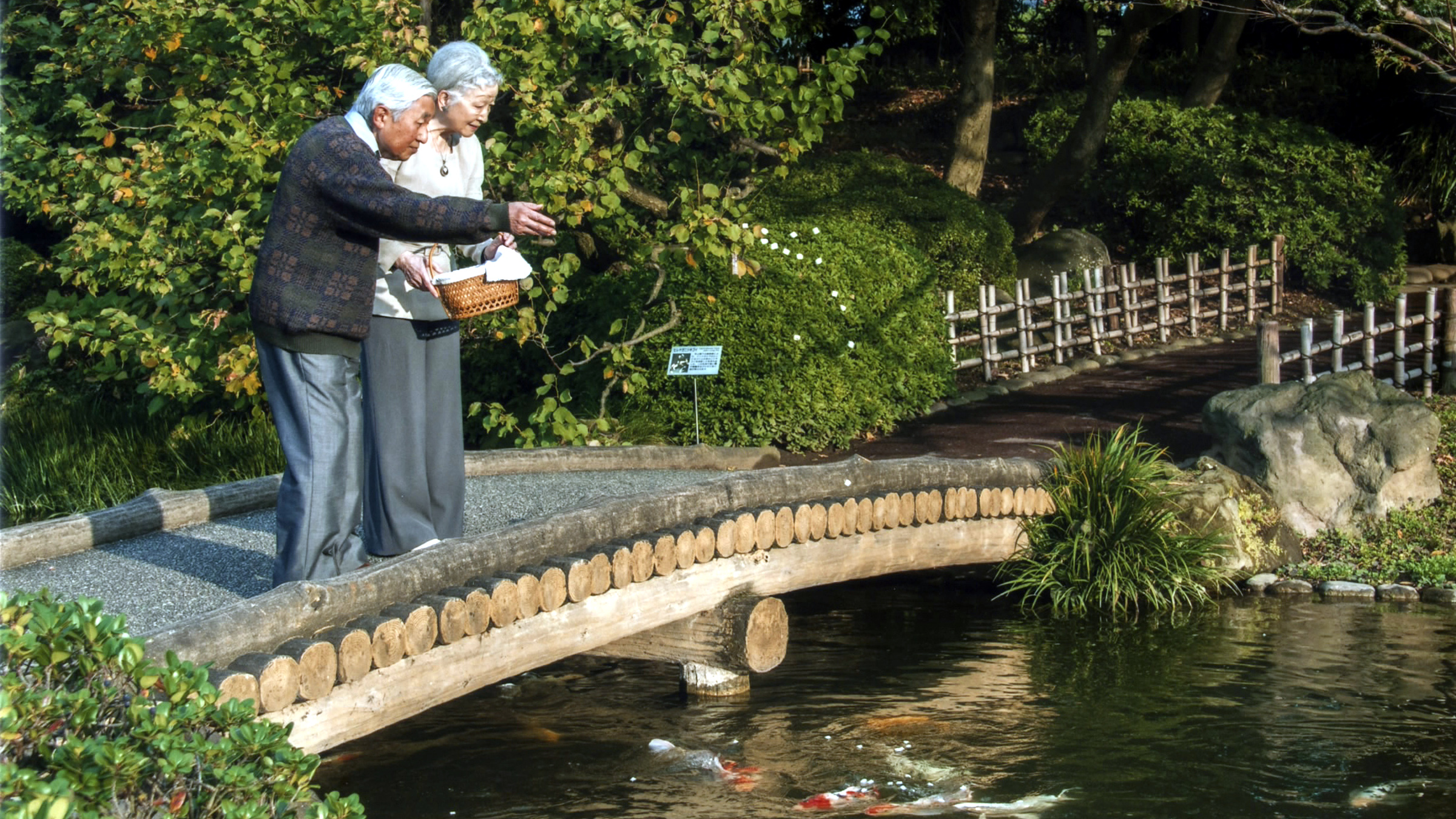 Japan's Emperor Akihito (L) feeds carp in a pond with Empress Michiko in the garden of the Imperial Residence at the Imperial Palace in Tokyo, in this handout picture taken October 27, 2014 and released by the Imperial Household Agency of Japan. Emperor Akihito celebrates his 81st birthday on December 23, 2014. Picture taken October 27, 2014. REUTERS/Imperial Household Agency of Japan/Handout via Reuters (JAPAN - Tags: ROYALS ANNIVERSARY)