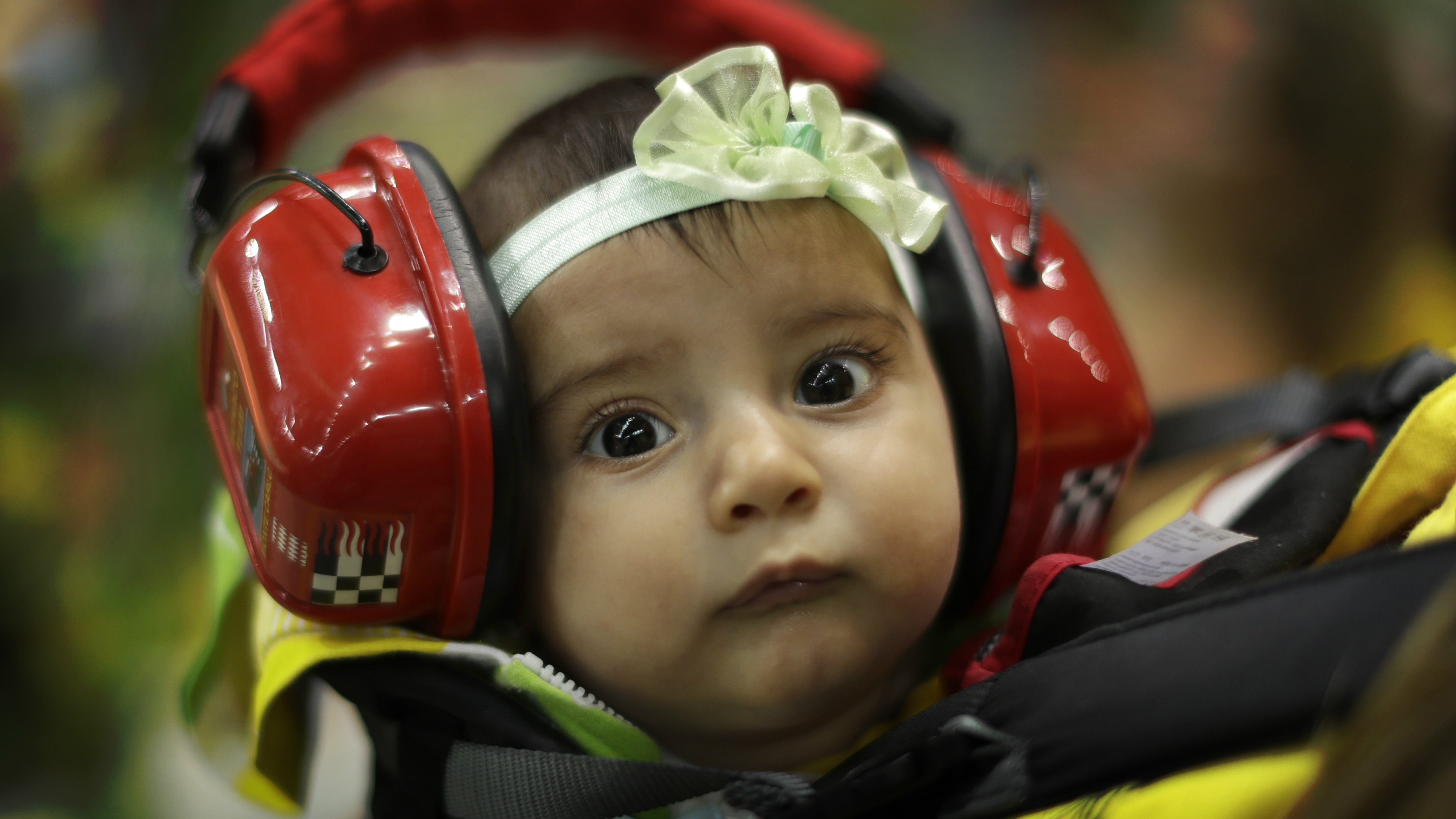 A baby girl hanging in a sling wears ear protectors