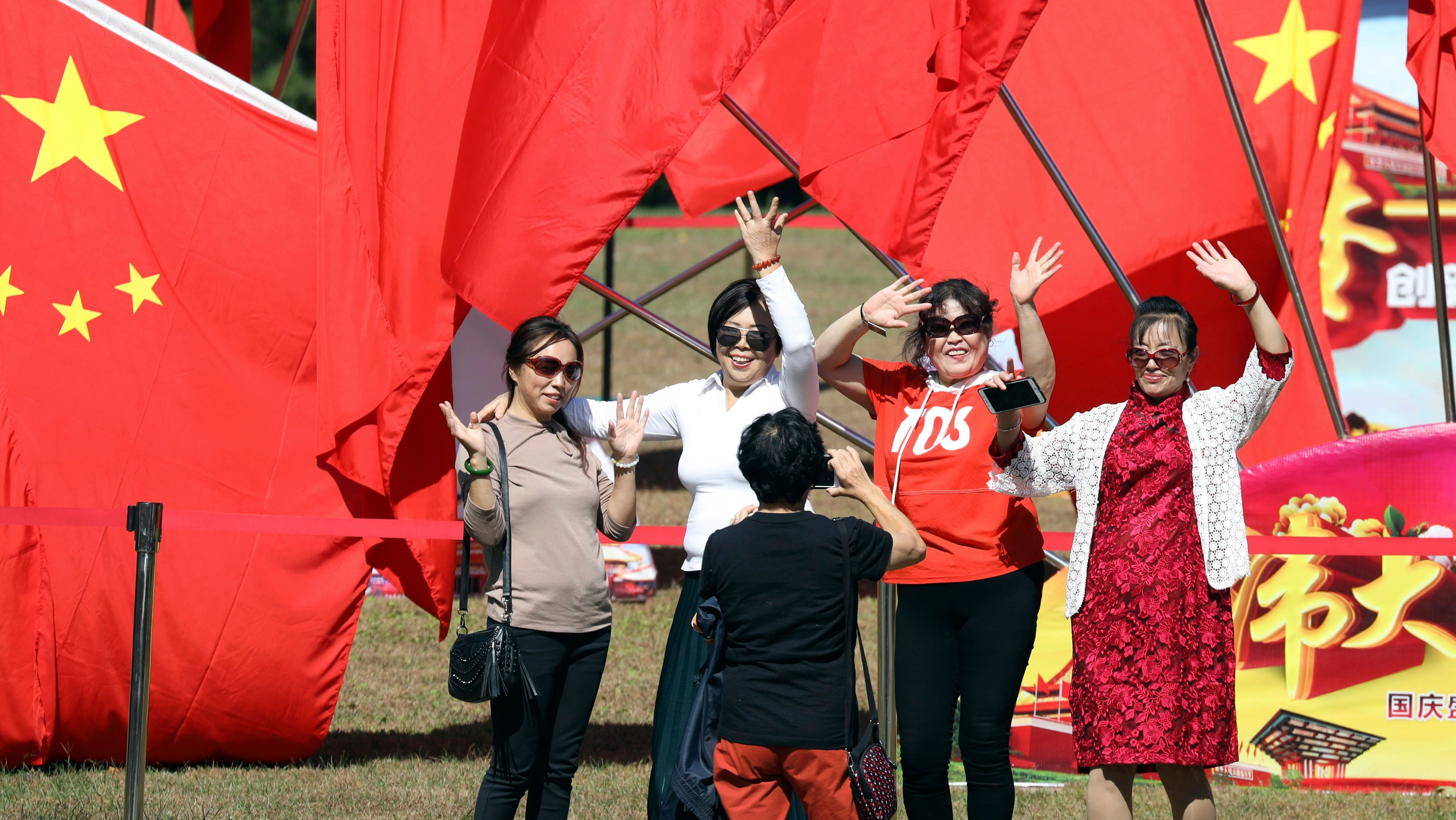 Women pose for photos near Chinese national flags flown to mark the National Day in Beijing, China Monday, Oct. 1, 2018. Chinese across the country are enjoying the week-long golden week holiday that coincides with the National Day celebrations.
