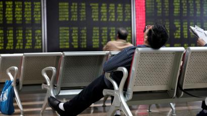 An investor takes a nap in front of a board showing stock information at a brokerage office in Beijing, China October 8, 2018. REUTERS/Jason Lee - RC1FB72E4E50