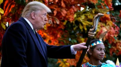U.S. President Donald Trump waves the staff of a child dressed as a pharaoh as he hands out Halloween candy to trick-or-treaters at the White House in Washington, U.S., October 28, 2018.