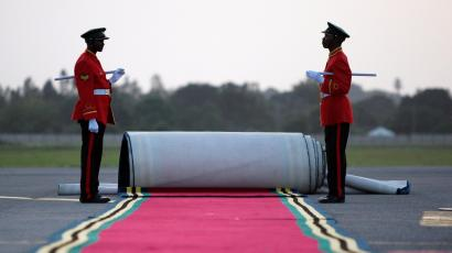 A pair of Tanzanian military guards prepare to roll out a red carpet as they await the arrival of U.S President George W. Bush at Julius Nyerere Airport in Dar Es Salaam February 16, 2008.