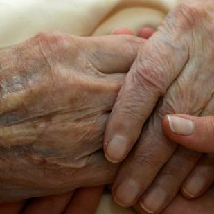 A young person holding the hands of an older person.