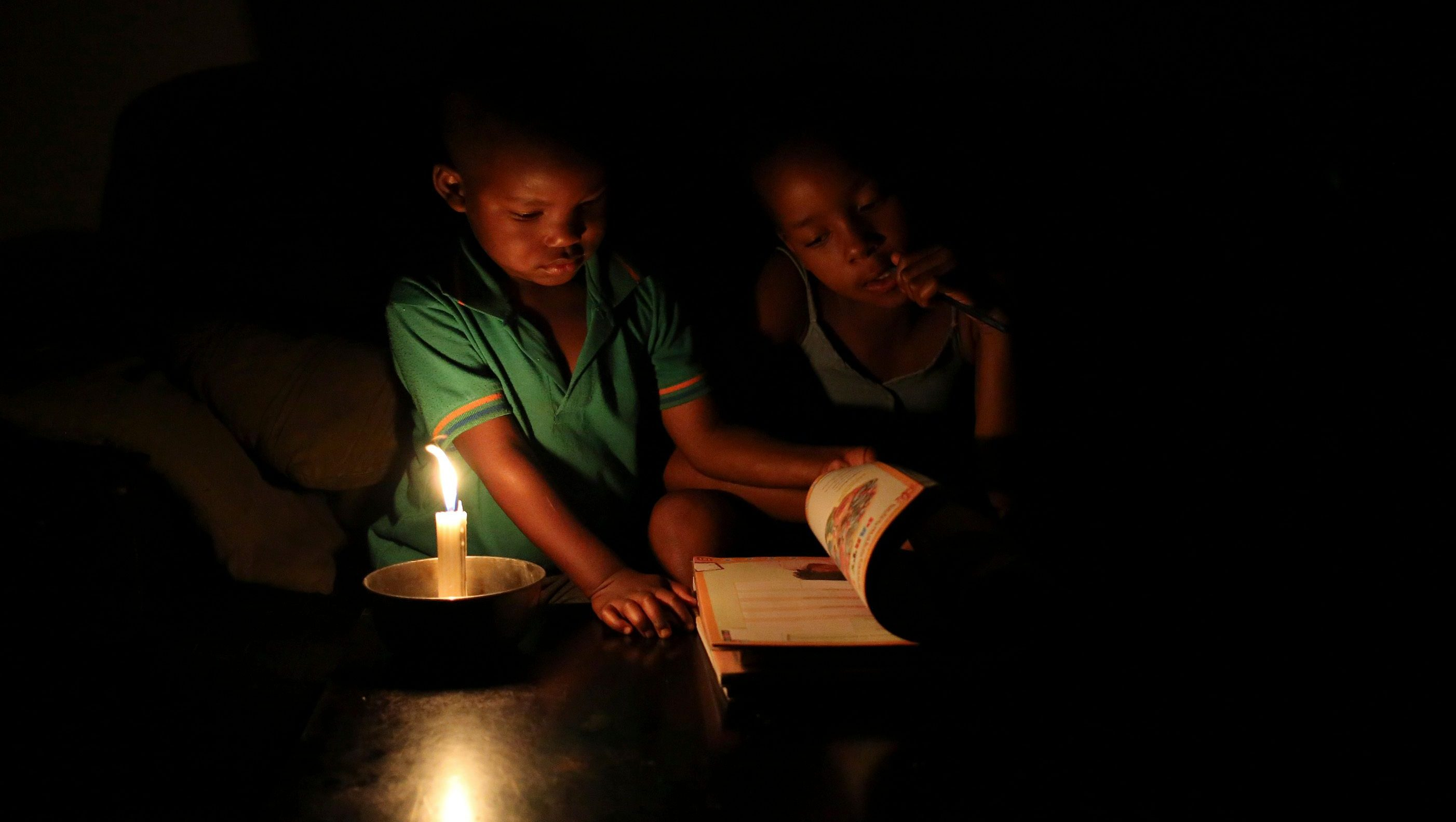 Sinovuyo Bhungane (R), 9, looks on as her studies are interrupted by her cousin Yonga, as she studies using candle light during load shedding in Soweto February 3, 2015. South Africa's power utility Eskom will implement rolling blackouts on Tuesday from 1500 GMT to 2000 GMT, the state-owned company said on its official Twitter account. (SOUTH AFRICA - Tags: ENERGY TPX IMAGES OF THE DAY BUSINESS) - GM1EB240A6N01