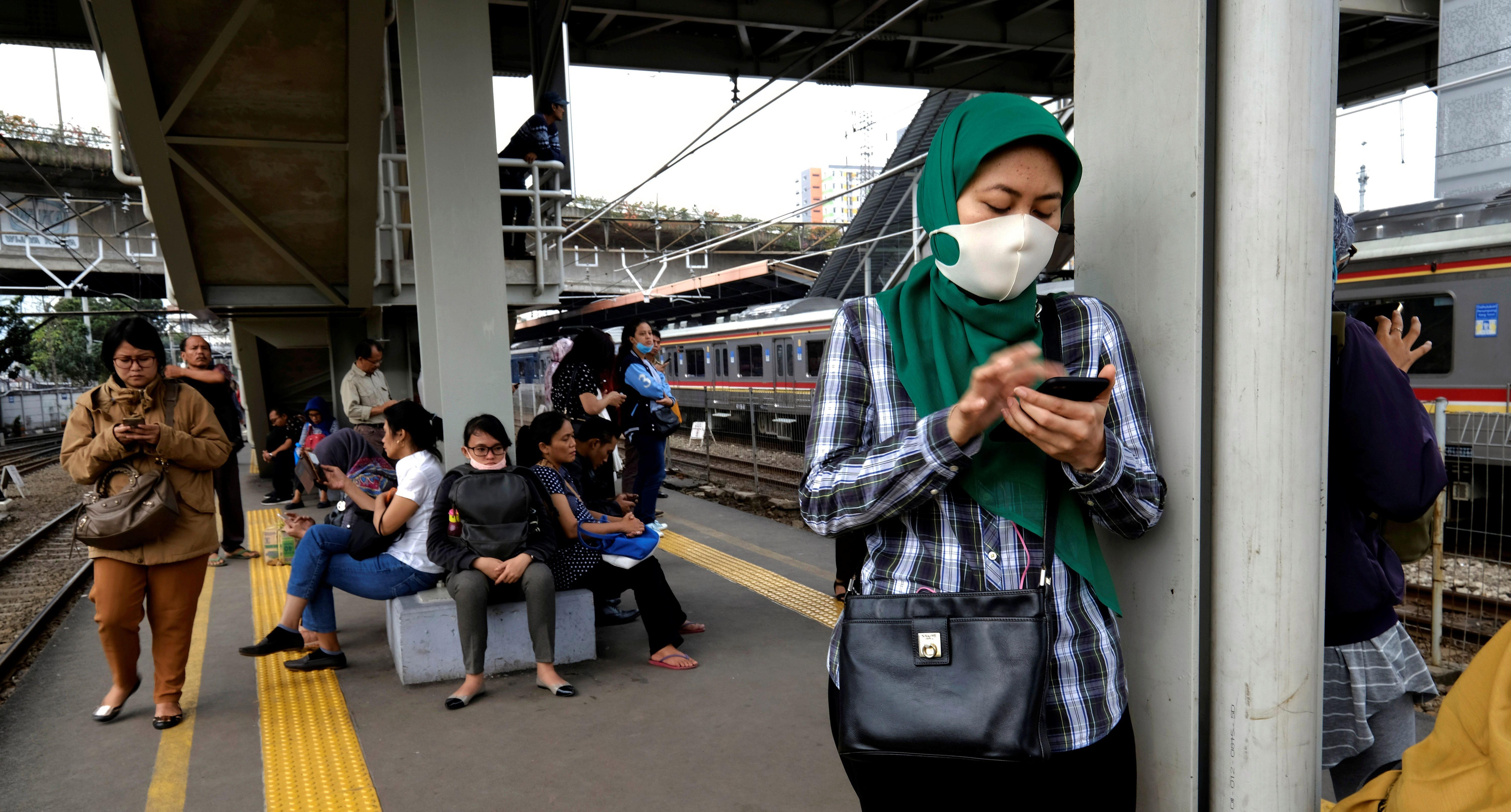 Commuters use their smartphones as wait their train during the morning rush at Tanah Abang train station in Jakarta