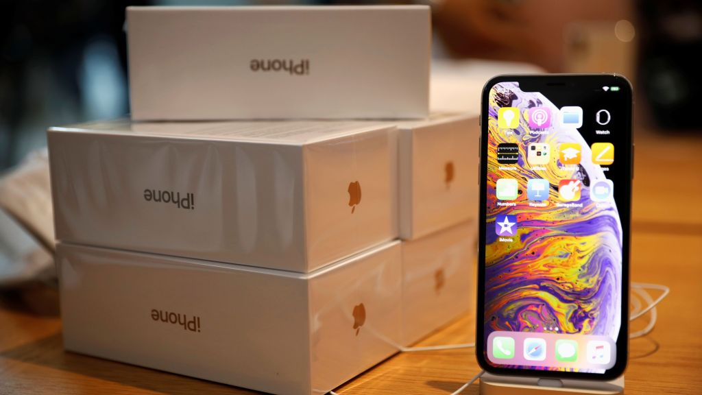 Boxes of iPhones purchased by customers are pictured next to an iPhone XS on display at the Apple Store in Singapore