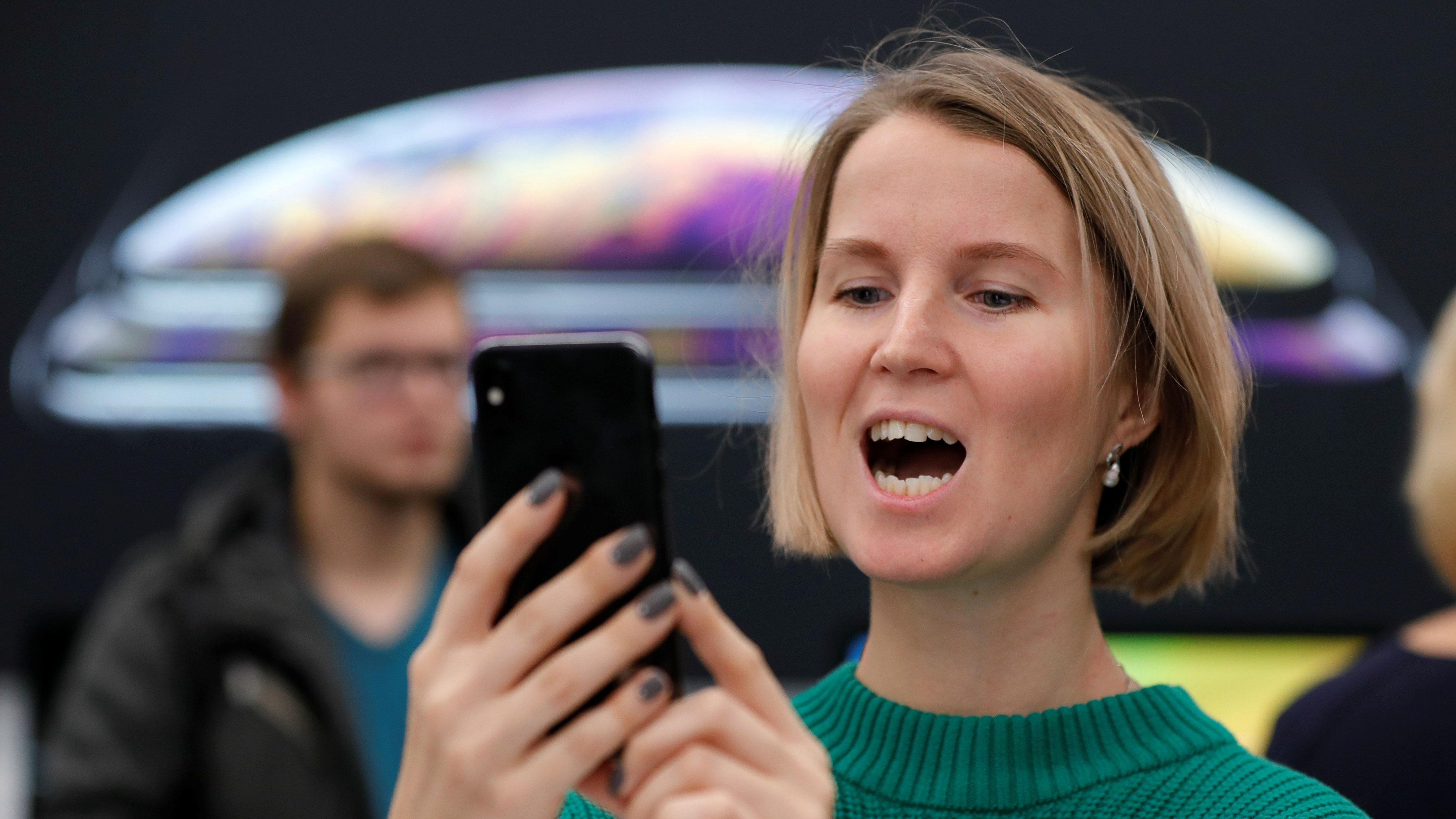 """A customer reacts during the launch of the new iPhone XS and XS Max smartphones sales at """"re:Store"""" Apple reseller shop in Moscow, Russia."""