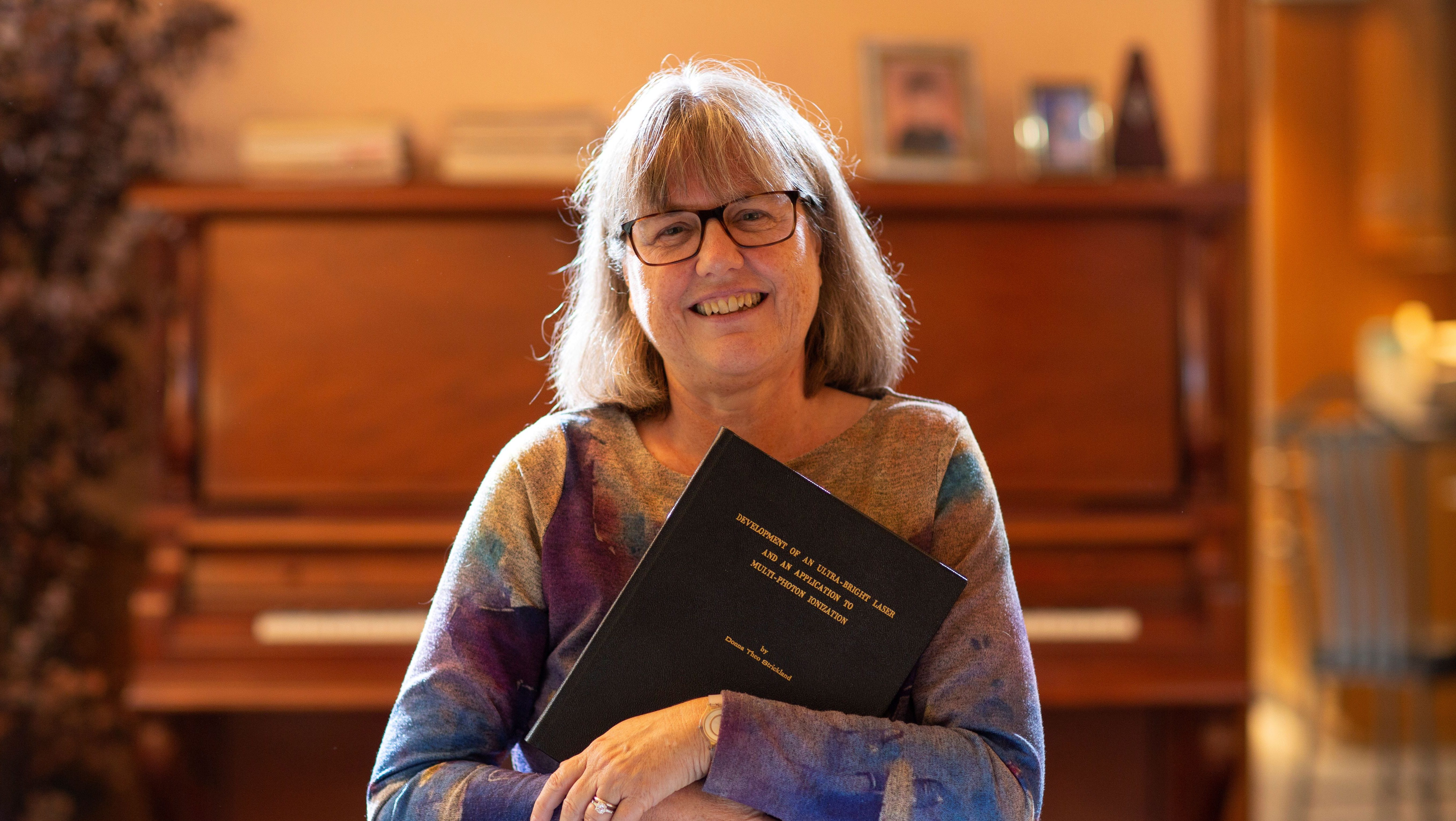 Donna Strickland, an associate professor at the University of Waterloo, poses with her paper that started her career 30 years ago, after winning the Nobel Prize for Physics at her home in Waterloo, Ontario, Canada October 2, 2018.