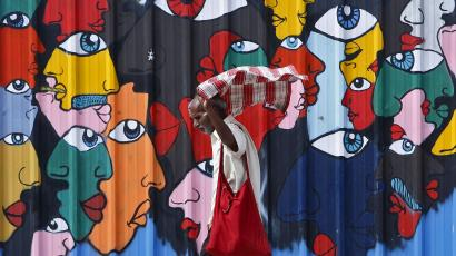 A commuter adjusts his scarf as he walks past a mural along a roadside in New Delhi