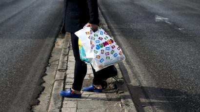 Woman holds a plastic bag with goods after exiting a Jumbo store in Athens