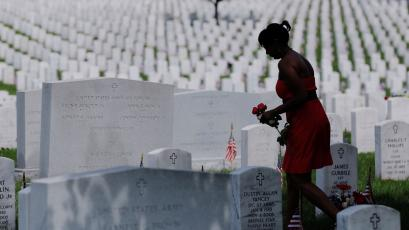A woman carries red roses as she walks among graves on Memorial Day at Arlington National Cemetery in Washington