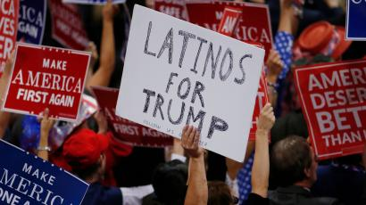 A person holds a sign reading 'Latinos for Trump'