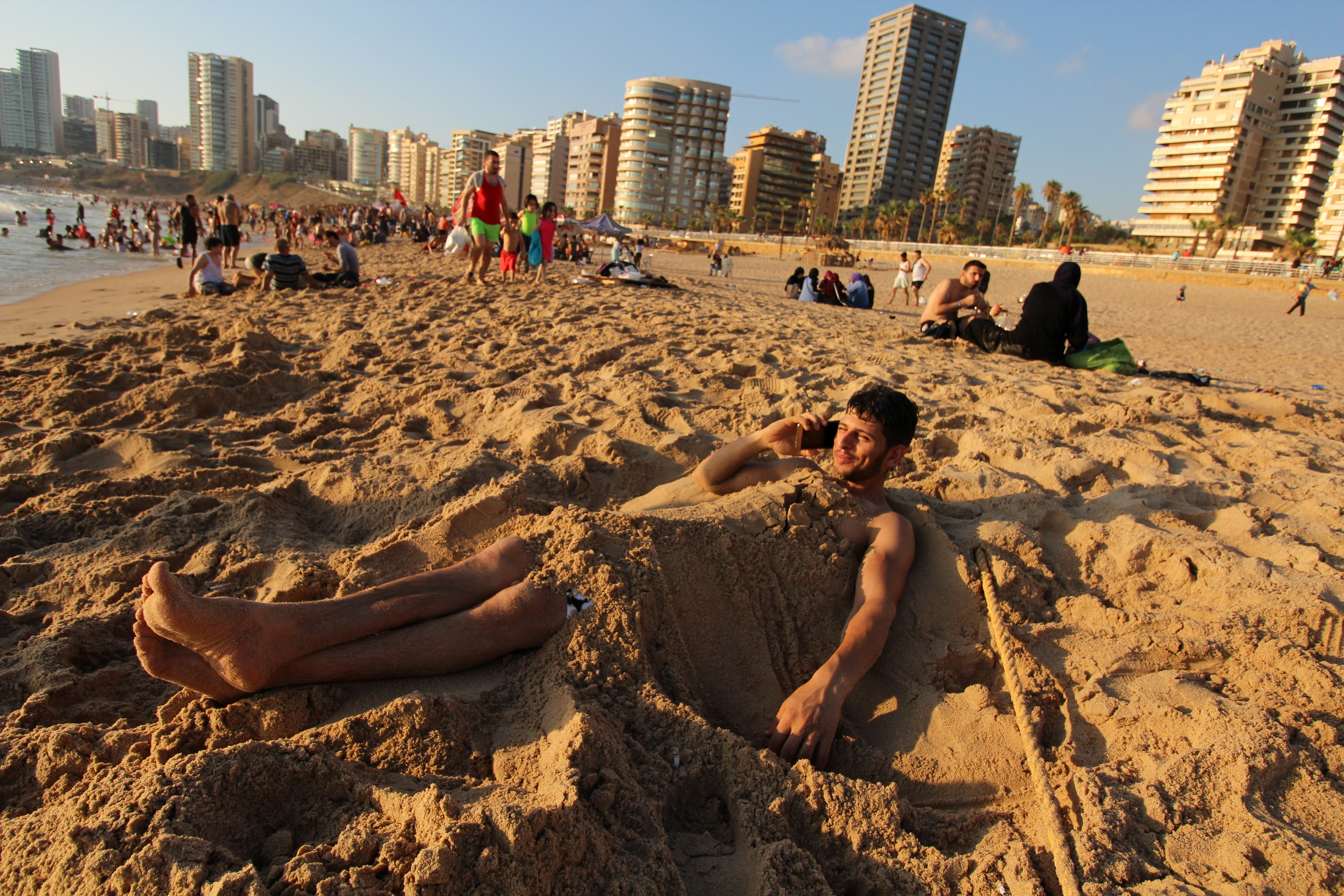 A man talks on his mobile phone while covered in sand on the beach in Beirut.