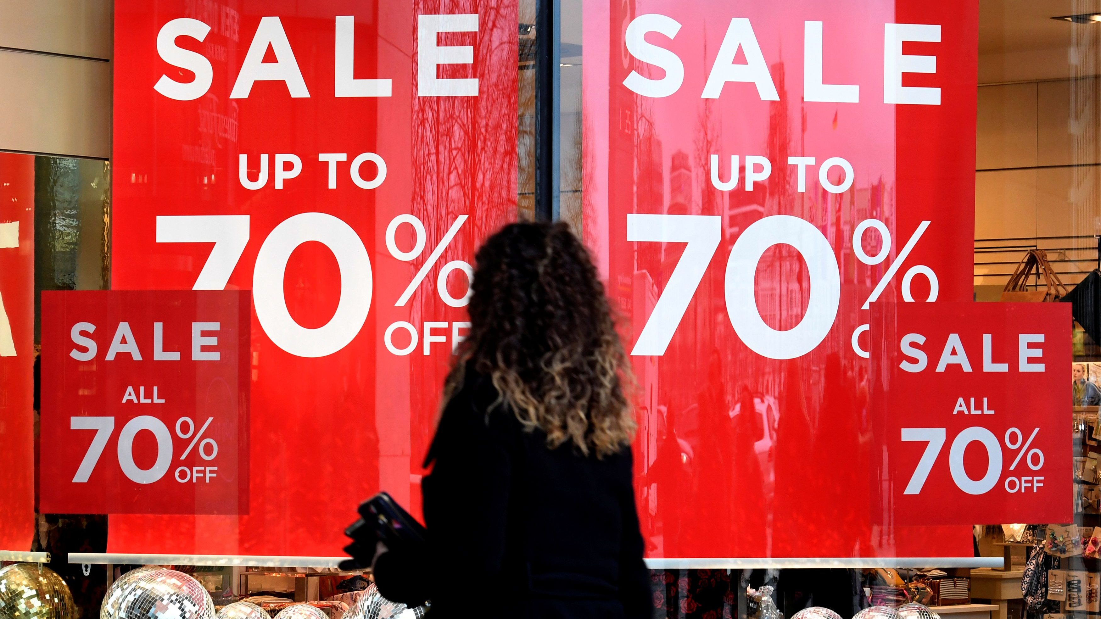 A woman passes sale signs in a shop window in downtown Hamburg