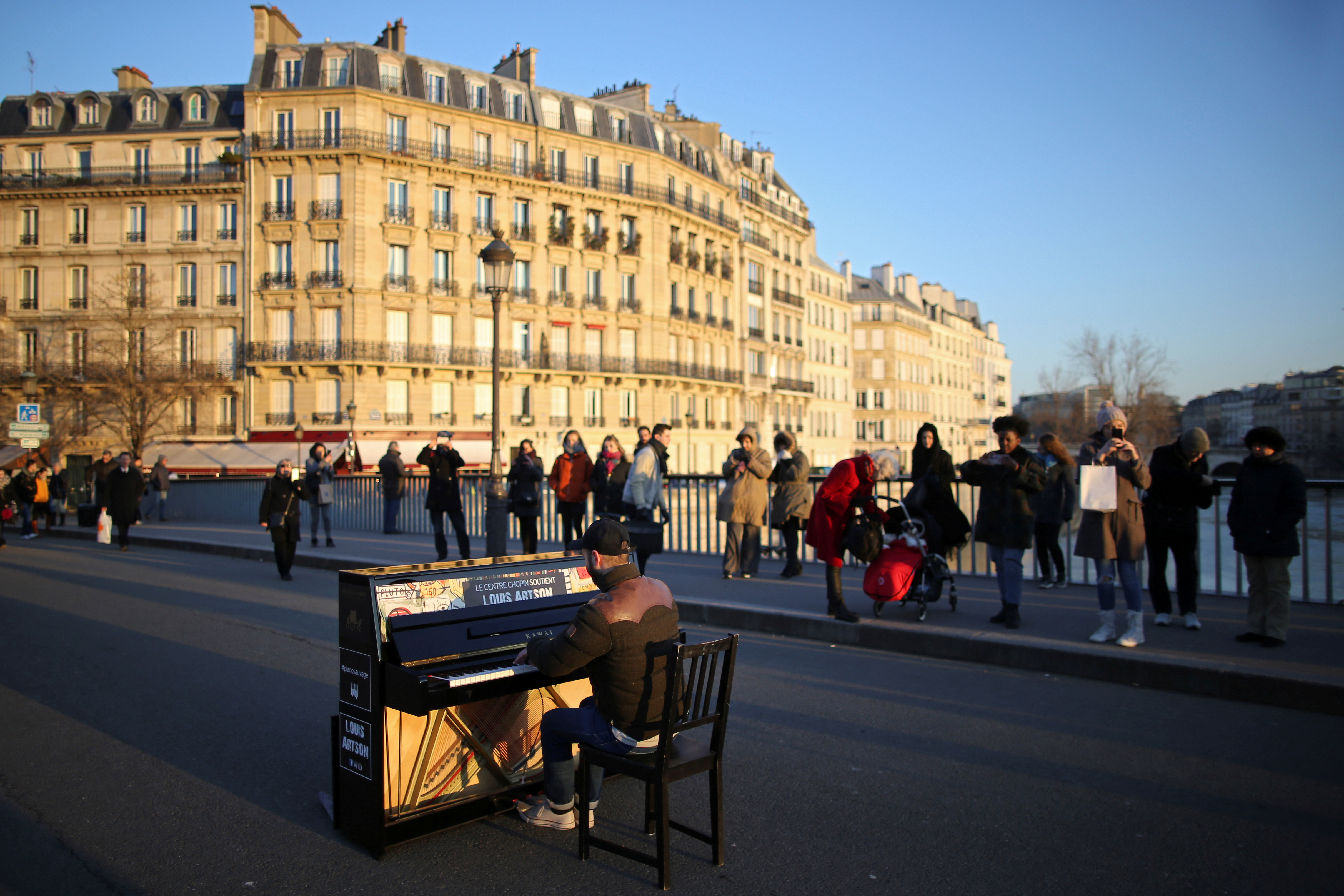 People stop to listen to a man who plays a piano on a bridge over the Seine River in central Paris