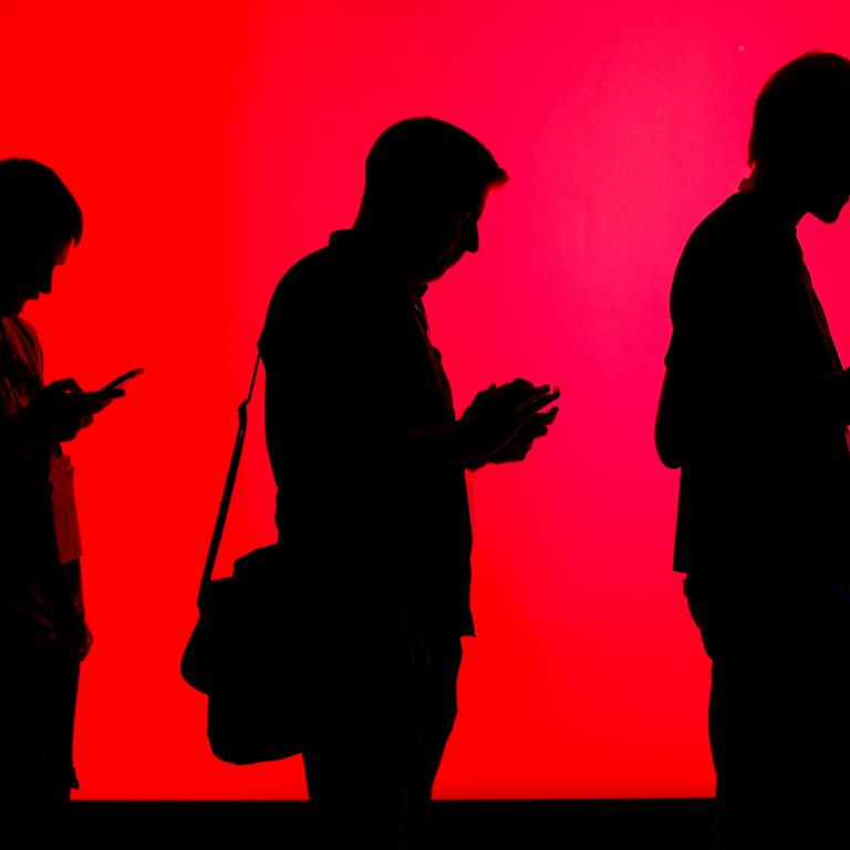Attendees look at their phones as they wait in line to check out new gaming software at E3.