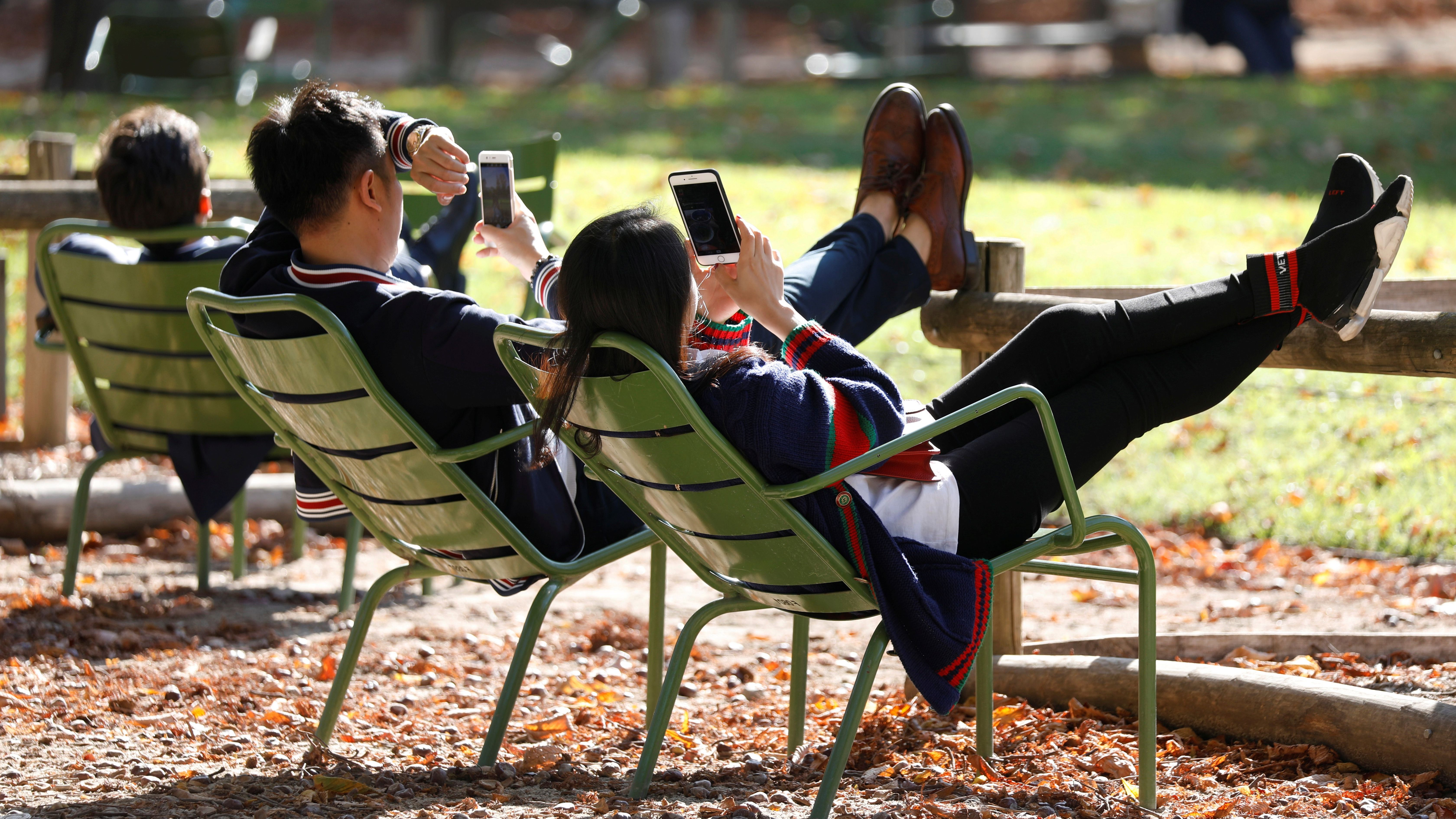 People look at the screen of their cell phones in the Jardin des Tuileries on an autumn day in Paris, France, October 8, 2018. REUTERS/Charles Platiau - RC1DCE912960