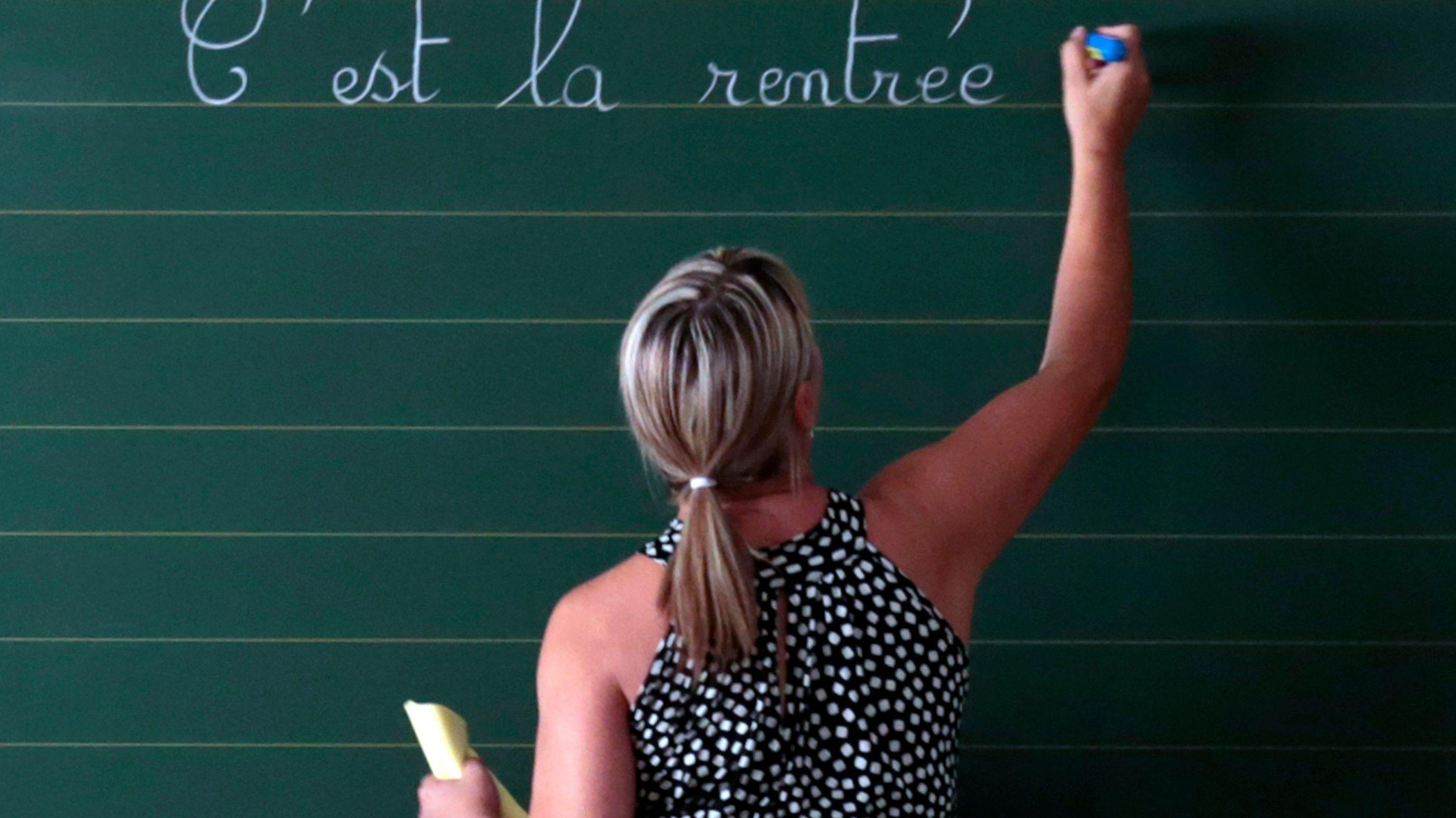A teacher writes on a board