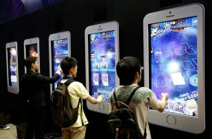 People play video games on mobile phone-shaped screens at Tokyo Game Show 2016