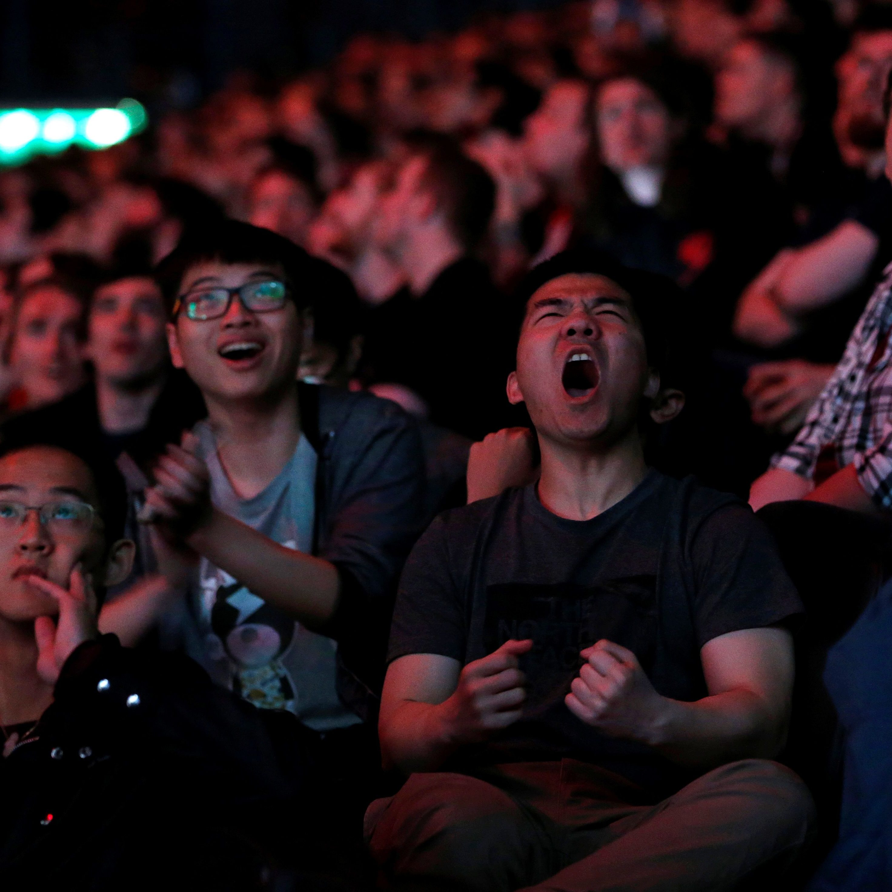 Esports fans react as they watch on from the stands.