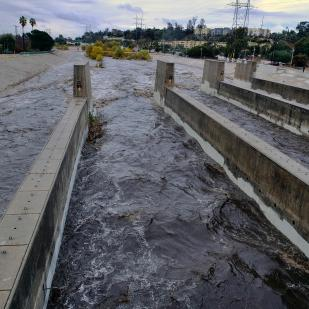 Rushing rainwater fills the Los Angeles river near downtown Los Angeles.