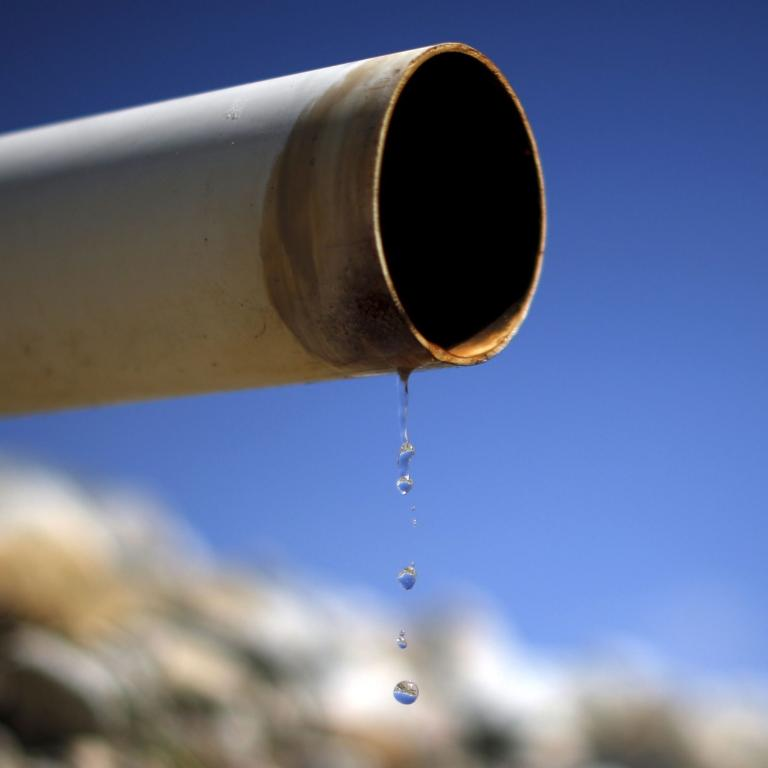 A dry pipe drips water on Gless Ranch in Kern County, California.