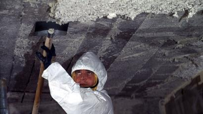 A worker scrapes asbestos from a school ceiling in France.