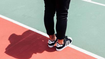 A person stands on a tennis court in sneakers and track pants