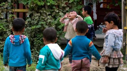 Uighur children play outdoors in Hotan, in western China's Xinjiang region. Uighurs fear the Chinese government's expansion of compulsory Mandarin-intensive classes and boarding schools away from home will gradually erode their children's Central Asian ethnic identity and Islamic beliefs Orphans Of The State, Hotan, China - 30 Aug 2018