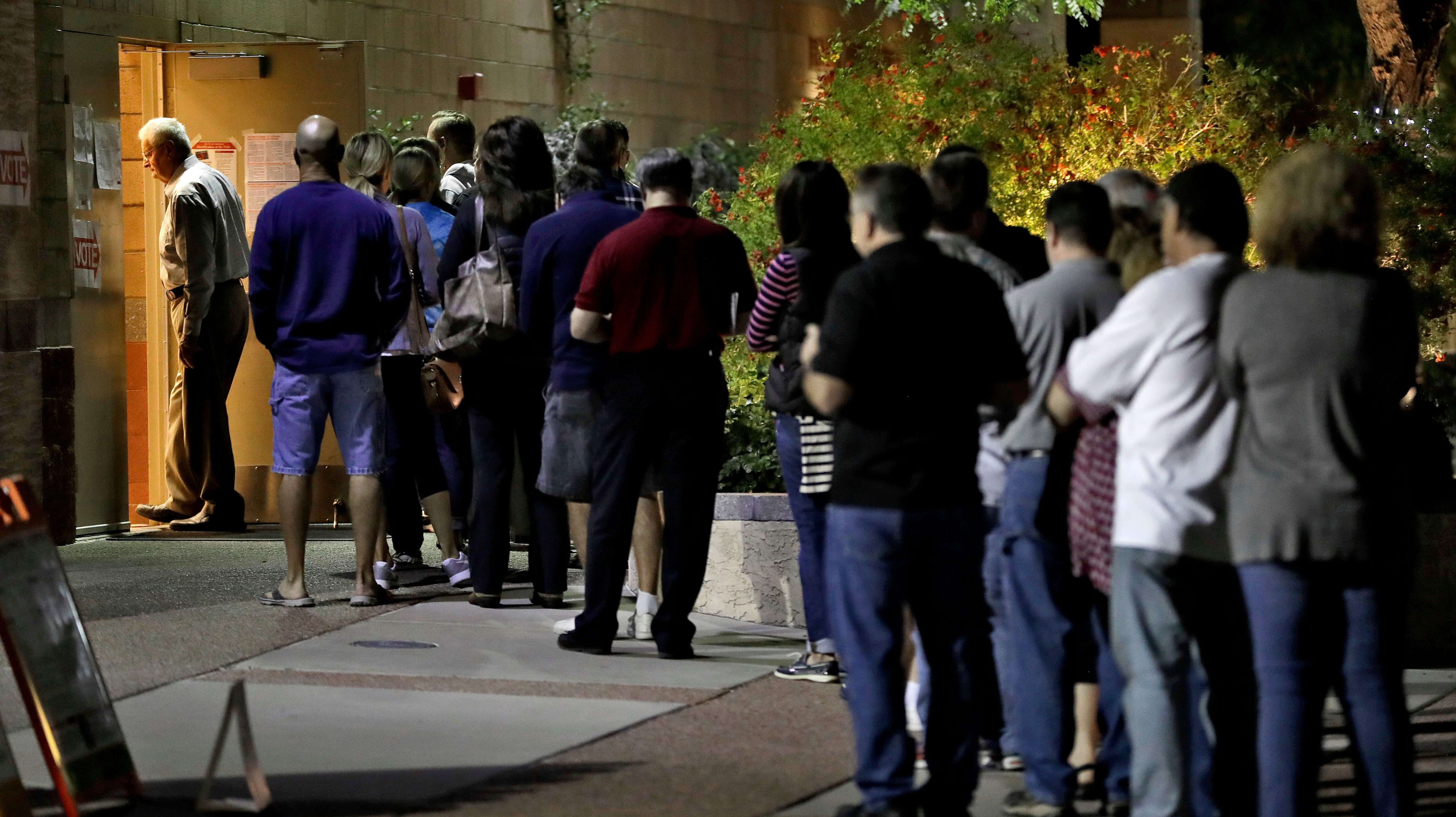 Voters wait in line to vote early Tuesday, Nov. 8, 2016, in Phoenix.