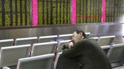 An man takes a nap in front of an electronic board showing stock information