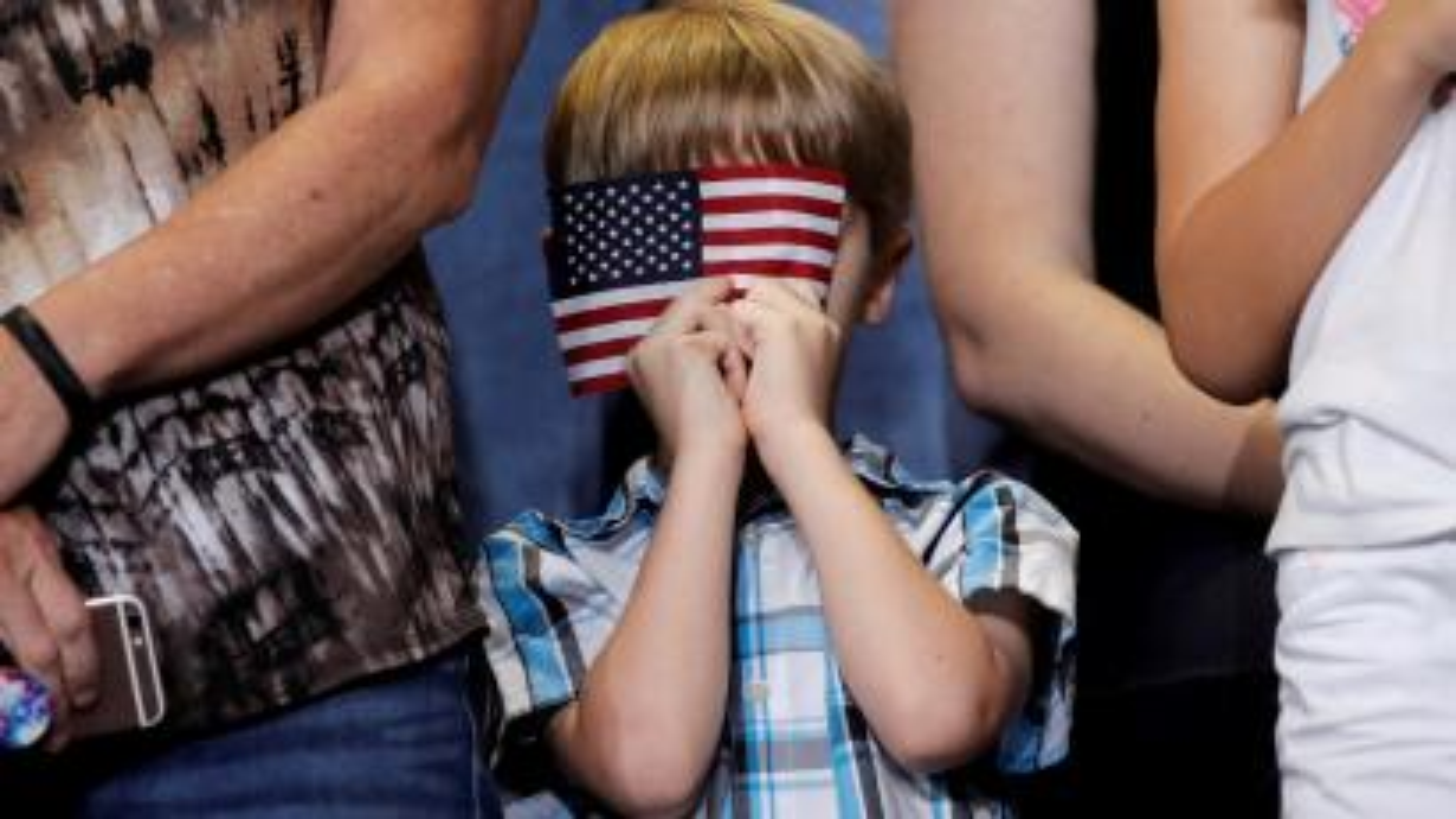 Boy hides behind US flag.